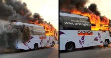 Orange travel bus catches fire.